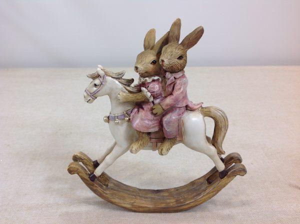 Coppia di conigli su cavallo a dondolo in resina