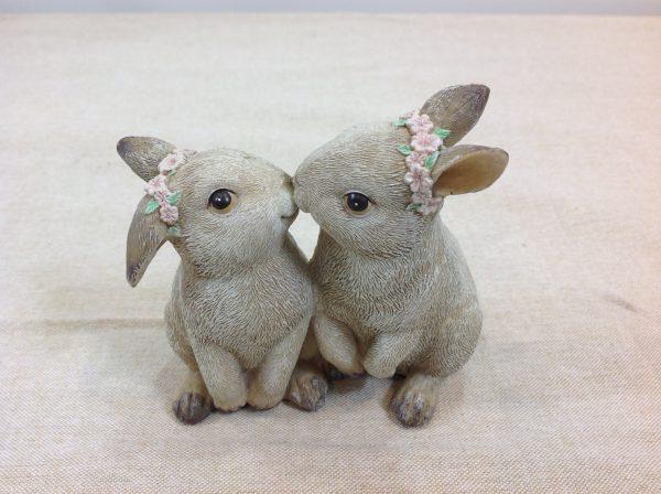 Coppia di conigli in resina che si baciano