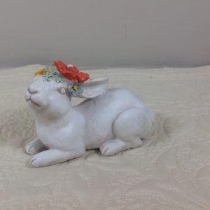 coniglio sdraiato in resina panna con fiori in testa